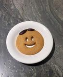 Uma cookie do sorriso na placa branca na tabela de mármore foto de stock royalty free