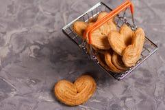 Uma cookie no formulário do coração perto do lote das cookies no metal croma a cesta do mercado com os punhos de borracha alaranj fotografia de stock