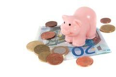 Uma cor-de-rosa piggy sobre notas de banco do euro da economia Foto de Stock