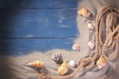 Uma corda do mar com muitos shell diferentes do mar na areia do mar em um fundo de madeira azul fotos de stock