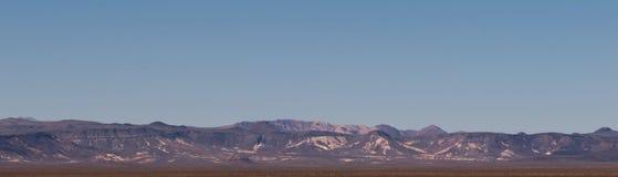 Uma cordilheira distante sob um céu azul Fotografia de Stock