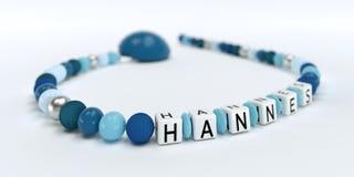Uma corrente azul da chupeta para meninos com nome Hannes Imagens de Stock