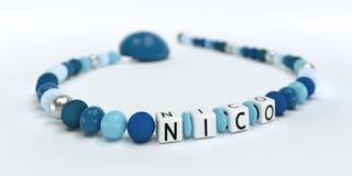 Uma corrente azul da chupeta para meninos com nome Nico Fotos de Stock
