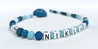 Uma corrente azul da chupeta para meninos com nome Niklas Imagens de Stock Royalty Free