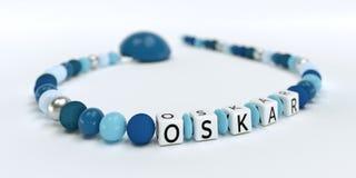 Uma corrente azul da chupeta para meninos com nome Oskar Fotos de Stock