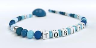 Uma corrente azul da chupeta para meninos com nome Tobias Foto de Stock