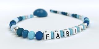 Uma corrente azul da chupeta para meninos com o nome Fabian Foto de Stock Royalty Free