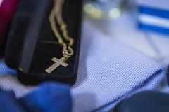 Uma corrente e uma cruz dourada em uma caixa em um fundo azul imagem de stock