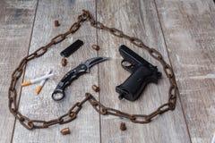 Uma corrente, pistola, cartuchos, uma faca e cigarros com um isqueiro preto imagem de stock royalty free