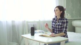 Uma cortina, jovem mulher bonita cega lê um livro, usa um assistente da voz, tem uma pergunta