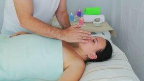 Uma cosmetóloga masculina dá a uma cliente uma massagem facial em um salão spa vídeos de arquivo