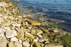 Uma costa com seixo e água do oceano. foto de stock