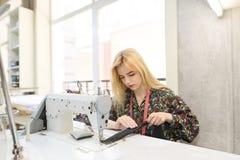 Uma costureira bonito senta-se no local de trabalho e nos trabalhos em uma máquina de costura em um estúdio brilhante fotos de stock