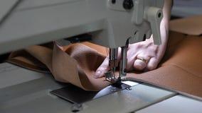 Uma costureira costura o couro preto em uma oficina costurando duas agulhas da m?quina de costura movem-se rapidamente para cima  vídeos de arquivo