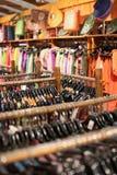 Uma cremalheira de camisas coloridas pendurou para a venda em uma feira Fotografia de Stock