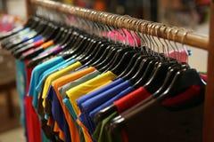 Uma cremalheira de camisas coloridas pendurou para a venda em uma feira Fotografia de Stock Royalty Free