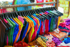 Uma cremalheira de camisas coloridas pendurou para a venda em uma feira Foto de Stock