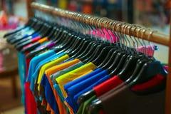 Uma cremalheira de camisas coloridas pendurou para a venda em uma feira Fotos de Stock Royalty Free