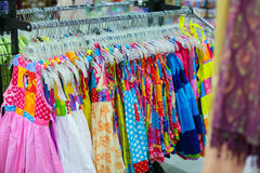 Uma cremalheira de camisas coloridas pendurou para a venda em uma feira Imagem de Stock Royalty Free
