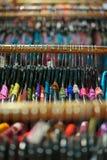 Uma cremalheira de camisas coloridas pendurou para a venda em uma feira Imagem de Stock