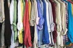 Uma cremalheira de camisas coloridas pendurou para a venda no mercado Fotos de Stock