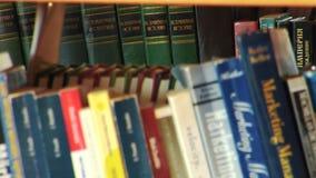 Uma cremalheira dos livros arranjados em uma biblioteca local vídeos de arquivo