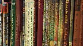 Uma cremalheira dos livros arranjados em uma biblioteca local filme