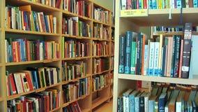 Uma cremalheira dos livros arranjados em uma biblioteca local video estoque