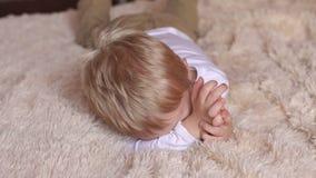 Uma criança alegre é jogada, ri e mostra a língua na cama filme