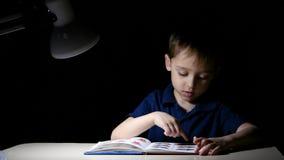 Uma criança aprecia sentar-se na noite em uma tabela iluminada por uma lâmpada, lendo um livro, pontos o dedo nos desenhos no liv video estoque