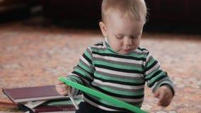 Uma criança atrativa joga em casa com uma régua plástica Guarda uma pena em suas mãos O menino é bebê de um ano filme