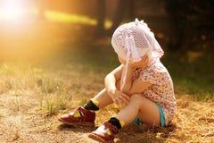 Uma criança bonita na luz do sol morna senta-se na terra fotografia de stock