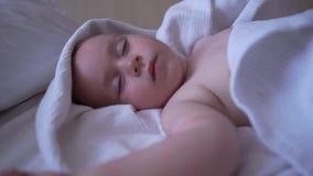 Uma criança bonito dorme com suas mãos acima em uma grande cama no movimento lento video estoque