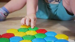 Uma criança bonito recolhe uma imagem dos grandes detalhes multi-coloridos Jogo com um enigma vídeos de arquivo