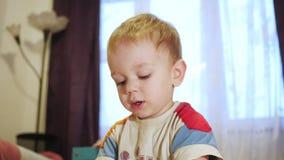 Uma criança bonito recolhe uma imagem dos grandes detalhes multi-coloridos Jogo com um enigma video estoque