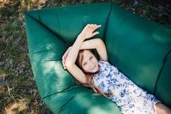 Uma criança coloca em um descanso em um sofá do ar na floresta Lamzac Curso, férias em família na floresta no verão Fotos de Stock Royalty Free