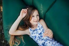Uma criança coloca em um descanso em um sofá do ar na floresta Lamzac Curso, férias em família na floresta no verão Foto de Stock