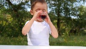 Uma criança com alegria bebe o suco da baga de um vidro de vidro em um fundo da natureza vídeos de arquivo
