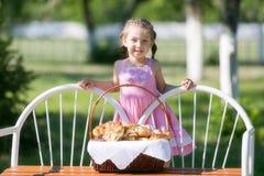 Uma criança com uma cesta do pão em um banco fotografia de stock royalty free