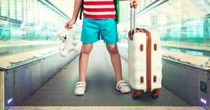 Uma criança com uma mala de viagem monta em uma escada rolante A primeira viagem imagens de stock