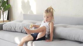 Uma criança com pão está sentando-se no sofá e está mastigando-se um naco branco