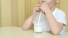 Uma criança com prazer bebe o leite de um vidro através de uma palha, sentando-se em uma tabela Mova a câmera da parte inferior p video estoque