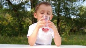 Uma criança com prazer bebe o suco da baga do vidro de vidro em um fundo da natureza vídeos de arquivo