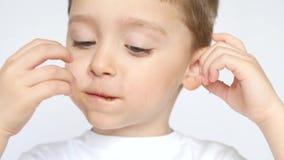 Uma criança com prazer e alegria que come microplaquetas de batata, em um fundo branco, close-up filme