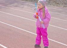 Uma criança com prazer e aplicação infla bolhas fotografia de stock
