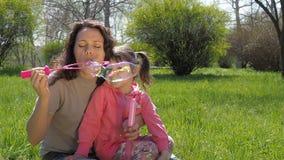 Uma criança com sua mãe está jogando com bolhas de sabão Uma família feliz no selvagem A mamã e a filha estão fundindo bolhas video estoque