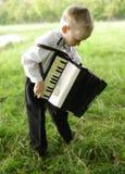 Uma criança com um acordeão em suas mãos fotografia de stock royalty free