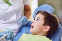 Uma criança com um dentista em um escritório dental fotos de stock
