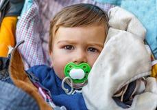 Uma criança com uma chupeta no transporte de bebê Fotos de Stock Royalty Free