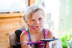 Uma criança com uma escova e pinturas Fotografia de Stock Royalty Free